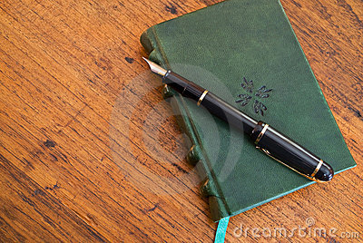 Pen and journal on wooden desk