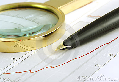 Pen and magnifying glass focusing on chart.