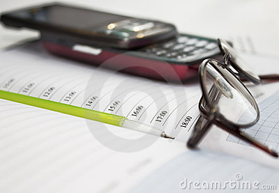 Pen, mobile phone and glasses in composition