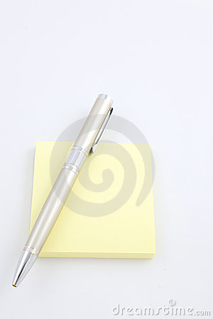 Pen on a yellow sticky note pad