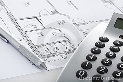 Pencil and calculator on blueprint of floor plan