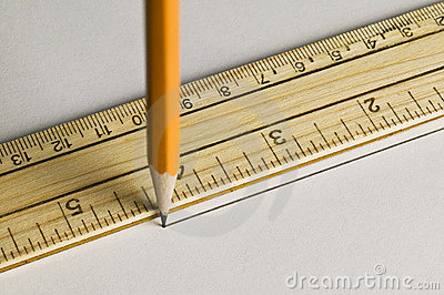Pencil drawing a straight line with a ruler