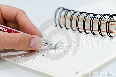 Pencil eraser, pencil eraser removing a written mistake on a piece of paper, delete, correct, and mistake concept. Closeup of penc Stock Photo