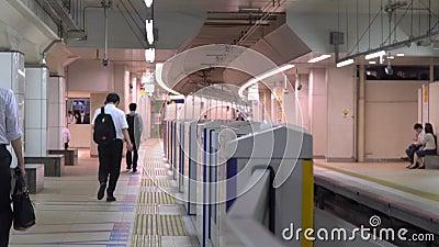 Pendlare som går på en plattform av den Shinjuku stationen i morgonen lager videofilmer
