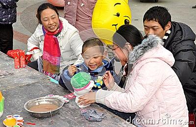 Pengzhou, China: Little Boy Painting Piggy Bank Editorial Stock Photo