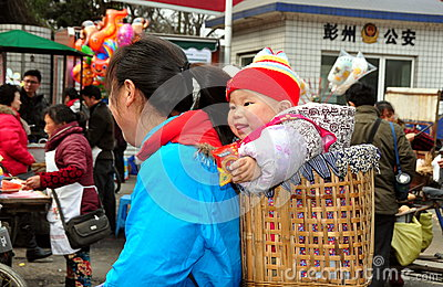 Pengzhou, China: Mother and Baby in Basket Editorial Stock Photo
