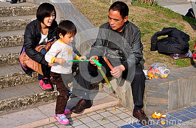 Pengzhou. China: Parents Playing with Son in Park Editorial Photo