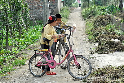 Pengzhou, China: Two Children with Bikes Editorial Image