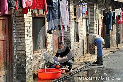 Pengzhou, China: Woman Doing Laundry on Old Street Editorial Stock Photo