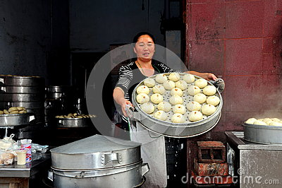 Pengzhou Kina: Kvinna med ångade Bao Zi Dumplings Redaktionell Arkivbild