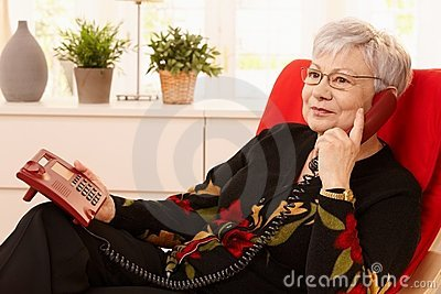 Pensioner woman using landline phone
