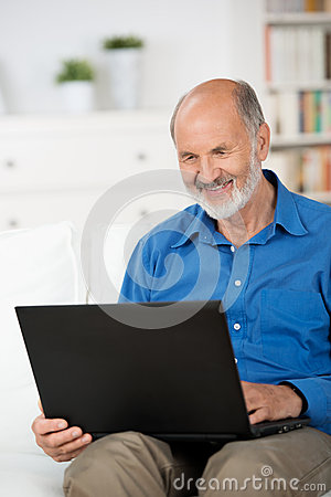 Pensioner working on a laptop at home