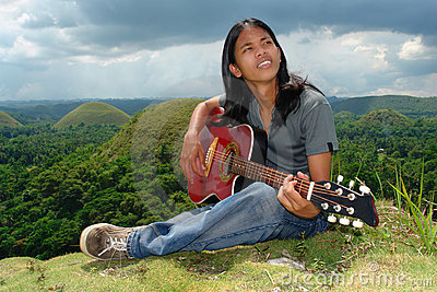 Pensive Asian hippie w guitar
