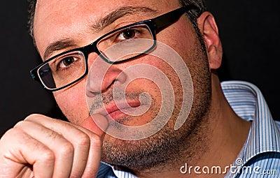 Pensive bearded caucasian man wearing eyeglasss