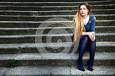 Pensive beautiful woman on stone steps