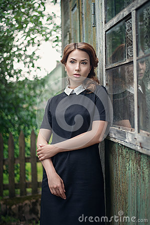 Free Pensive Beautiful Young Girl In Retro Style Dress Standing Near The Window Of Old Wooden House. Royalty Free Stock Photo - 79962725