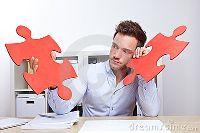 Pensive business man with jigsaw