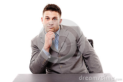 Pensive businessman sitting at the table with hand on chin