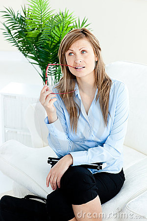 Pensive businesswoman holding glasses on a sofa