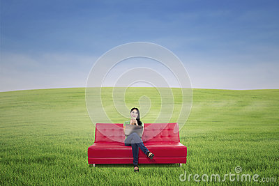 Pensive female having coffee on red sofa outdoor