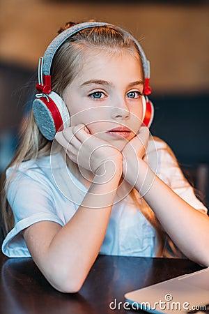 Free Pensive Little Girl Listening Music In Headphones Stock Photo - 94686690