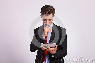 Pensive man holding tablet