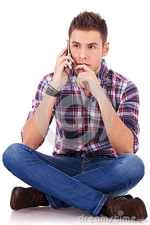 Pensive man sitting and talking on the phone