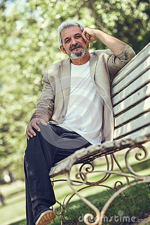 Free Pensive Mature Man Sitting On Bench In An Urban Park. Royalty Free Stock Image - 99989916