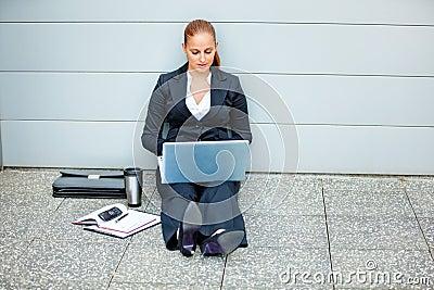 Pensive modern business woman using laptop