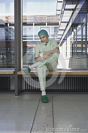 Pensive Physician With Coffee Cup In Hospital Corridor