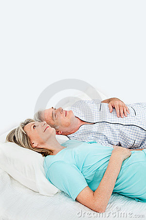 Pensive senior couple in bed