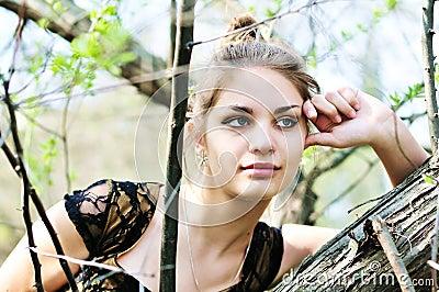 Pensive teen girl near the tree