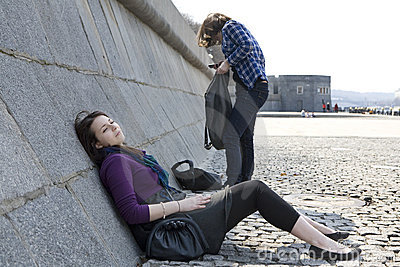 Pensive teen girls sitting at river