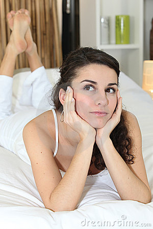 Pensive woman on bed