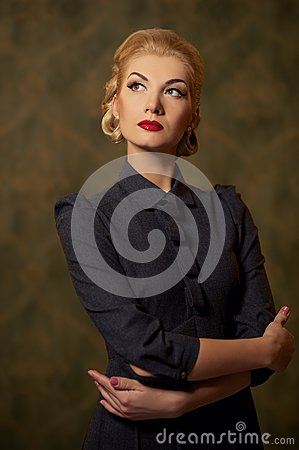 Pensive woman in grey dress with a retro make-up