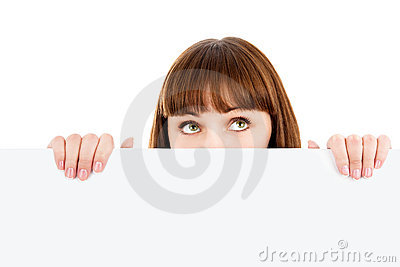 Pensive woman peeking over blank billboard