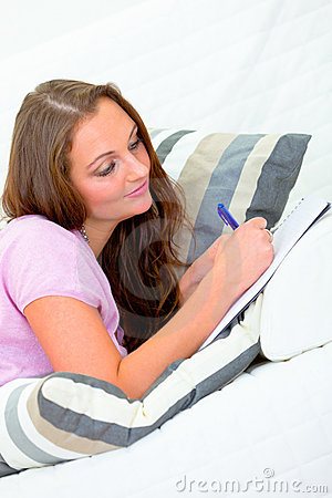 Pensive woman on sofa and writing in notebook