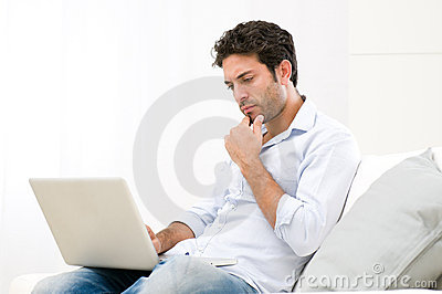 Pensive worried guy at laptop
