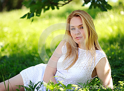 Pensive young woman lying in the green grass, enjoying summer day