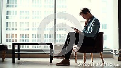 Pensjonalny młody przedsiębiorca siedzący na krześle i wykorzystujący nowoczesny gadżet zbiory wideo