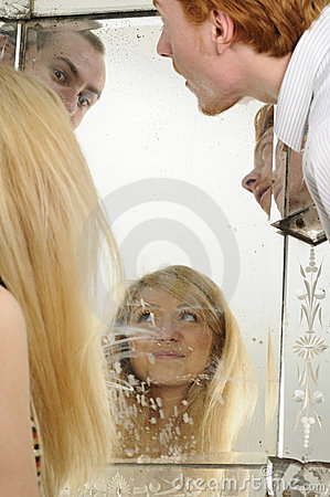 People admiring face in mirror