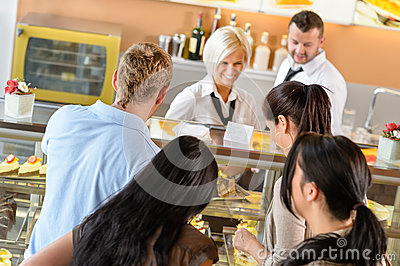 People buying cakes at cafeteria queue desserts