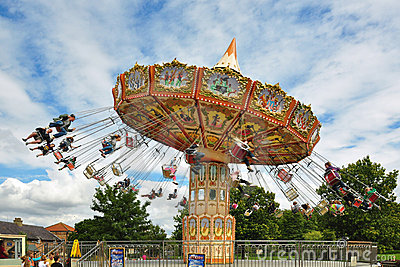 People on carousel under blue sky with clouds Editorial Image