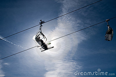 People in chairlift in front of bright sun