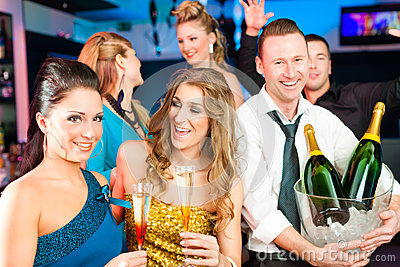 People in club or bar drinking champagne