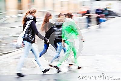 People crossing the street til it rains