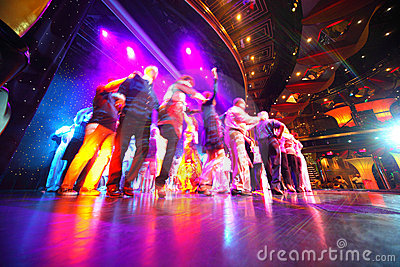 People crowd dance at an illuminated stage