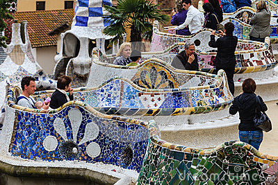 People enjoying mosaic tile benches in Parc Guell Editorial Stock Photo