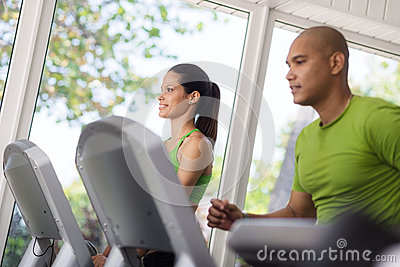 People exercising and running on treadmill in gym