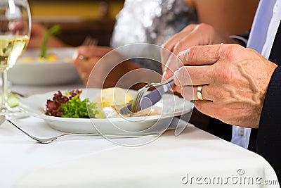 People fine dining in elegant restaurant